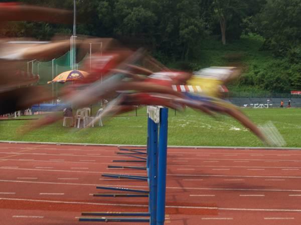 Movimento de salto dos atletas sobre a barreira nos 400 metros com barreira.